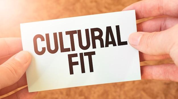 Iscrizione di parola cultural fit sul foglio di carta della carta bianca nelle mani di un uomo d'affari.
