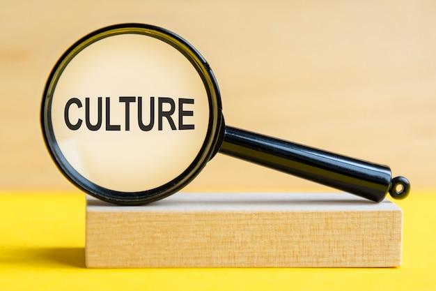 Parola di cultura attraverso la lente di ingrandimento su sfondo di legno. la lente d'ingrandimento è montata su un supporto di legno su un tavolo giallo