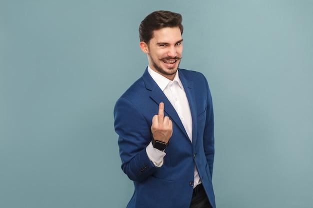 Astuto uomo d'affari che mostra il segno del cazzo alla telecamera e sorride. concetto di uomini d'affari, riccamente e successo. interno, girato in studio su sfondo azzurro