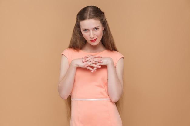Piano astuto, guardando la fotocamera. ritratto di donna emotiva carina e bella con trucco e capelli lunghi in abito rosa. indoor, girato in studio, isolato su sfondo marrone chiaro o beige.