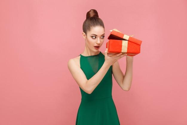 Donna astuta che apre una scatola regalo rossa guardando dentro