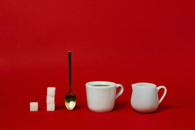 Tazza di americano, cucchiaio d'oro, crema e tazze di zucchero sul rosso