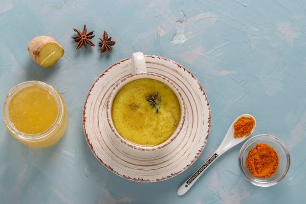 Tazza di latte ayurvedico dorato alla curcuma con polvere di curcuma, cannella, zenzero e anice stellato su superficie azzurra, vista dall'alto
