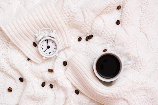 Tazza di caffè nero, sveglia e chicchi di caffè su un accogliente maglione bianco. è ora di bere il concetto di caffè. vista dall'alto