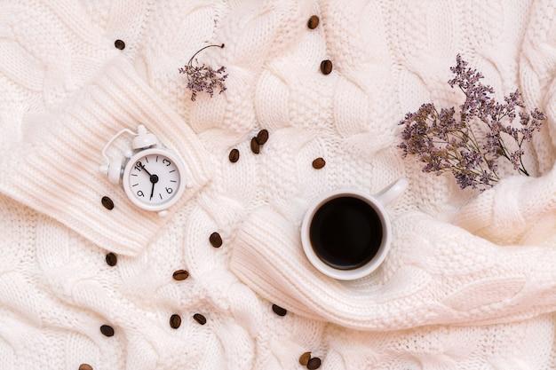 Una tazza di caffè nero, una sveglia, fiori secchi e chicchi di caffè su un accogliente maglione bianco. concetto di tempo di benessere. vista dall'alto