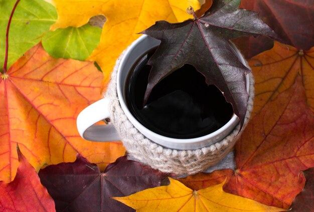 Una tazza di caffè nero nel fogliame luminoso di autunno. i colori allegri dell'autunno
