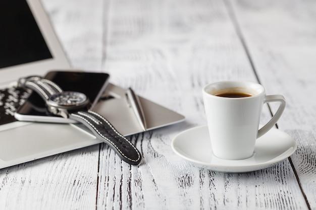 Una tazza di caffè nero e abiti casual business su tavola di legno sfondo,