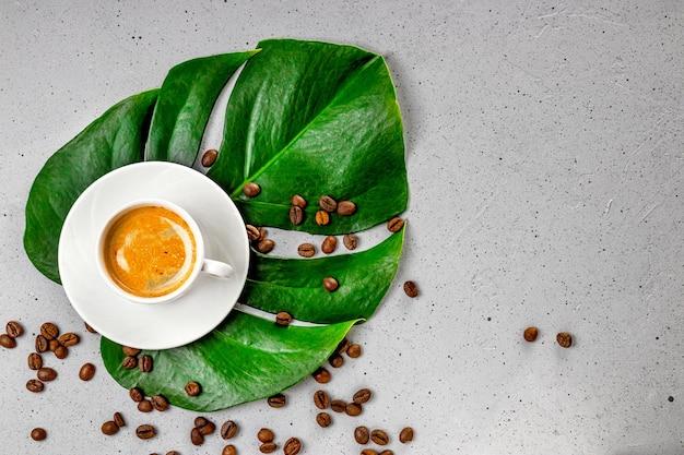 Tazza di caffè nero e chicchi di caffè sulla foglia di monstera e vista dall'alto di sfondo grigio cemento.