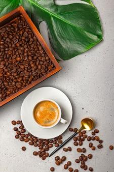 Tazza di caffè nero, chicchi di caffè nella scatola di legno e foglia di monstera sullo sfondo grigio cemento