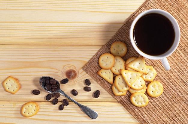 Tazza di caffè nero e cracker con sapore di formaggio per colazione su tavola di legno, vista dall'alto