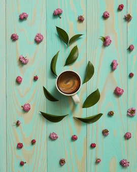 Tazza di caffè nero decorata con fiori rosa e foglie piatte