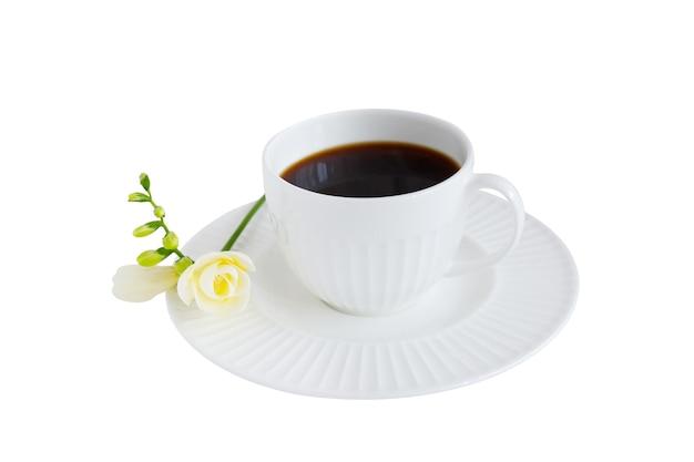 Tazza di caffè nero e fiore di fresia isolati su sfondo bianco