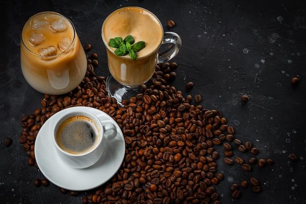 Tazza di caffè nero, un bicchiere di caffè freddo, un bicchiere di latte e chicchi di caffè tostati su sfondo grigio scuro.