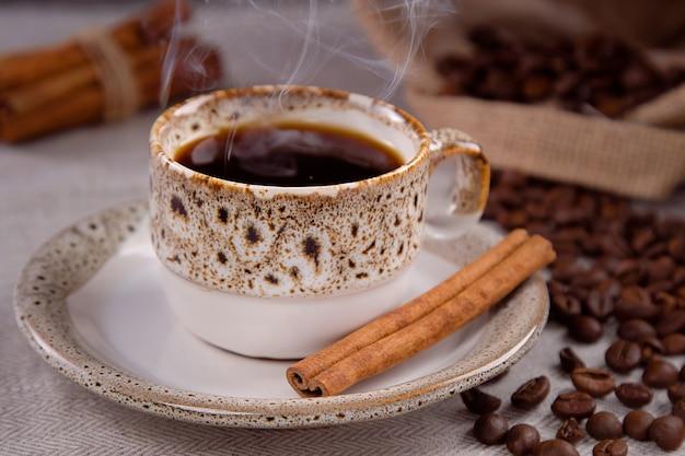 Tazza di caffè nero e chicchi di caffè con bastoncini di cannella.