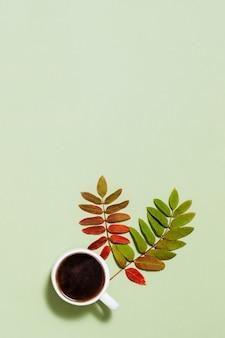 Tazza di caffè nero e foglie autunnali gialle rosse su carta verde pastello