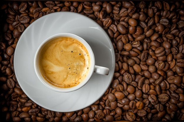 Tazza di caffè nero e chicchi di caffè tostati vista dall'alto.