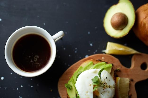 Tazza di caffè nero e panino con avocado e semi di uovo in camicia e microgreen superficie nera copia spazio healthy breackfast