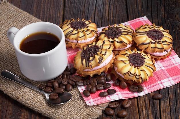 Tazza di caffè nero e biscotti di pasta frolla con cioccolato e crema su tavola in legno rustico