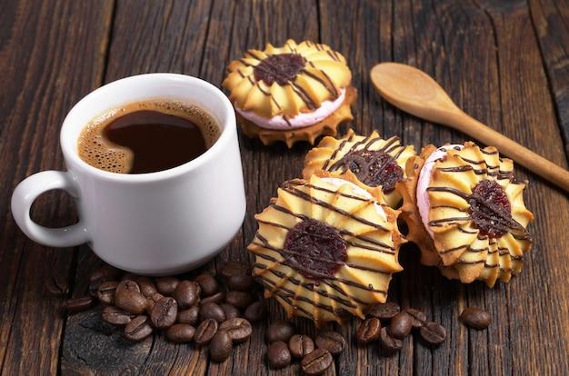 Tazza di caffè nero e biscotti di pasta frolla con crema e cioccolato su un tavolo di legno