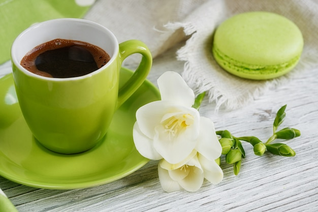 Tazza di caffè nero, fiori bianchi di fresia e dolci amaretti francesi pastello