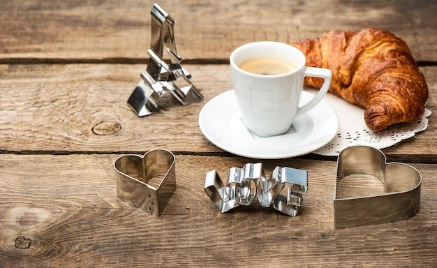 Tazza di caffè nero con croissant e decorazione a cuore su fondo di legno rustico