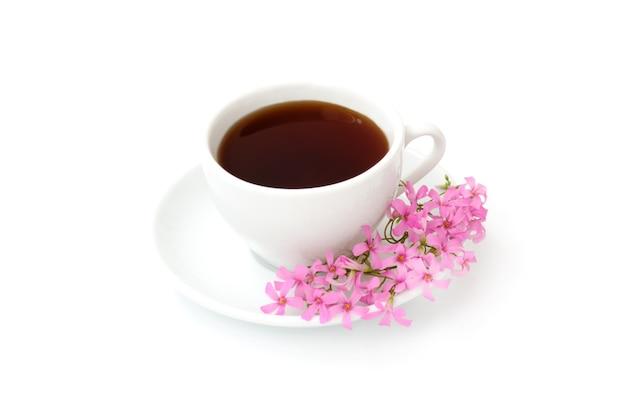 Una tazza di caffè nero con fiori su sfondo bianco
