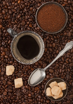 Tazza di caffè nero con caffè macinato e zucchero di canna con cucchiaio d'argento all'interno di chicchi di caffè freschi sullo sfondo. vista dall'alto