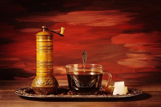 Una tazza di caffè nero con un macinino da caffè manuale, zollette di zucchero e chicchi di caffè sul tavolo