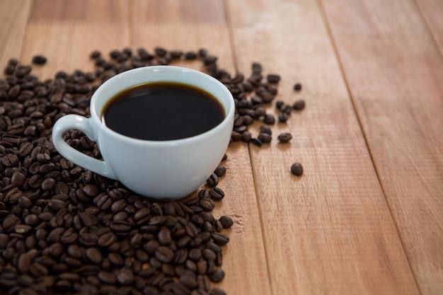 Tazza di caffè nero con chicchi di caffè tostati