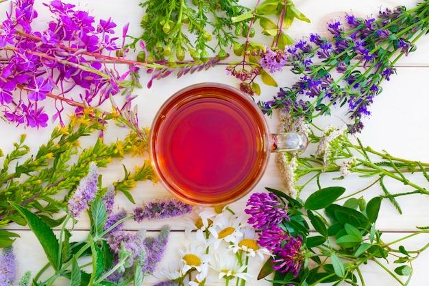 La tazza di tisana nera con rami di erbe medicinali sulla tavola di legno