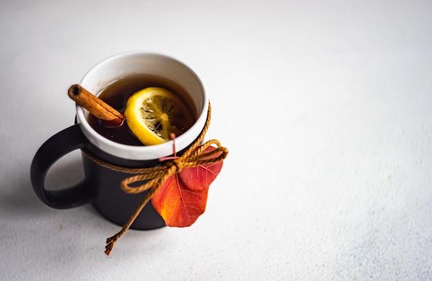 Tazza di tè nero e limone su fondo di legno con lo spazio della copia