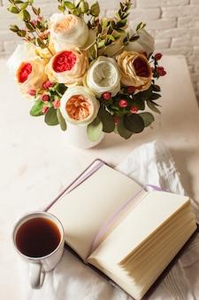 Una tazza di tè nero, taccuino e bellissimi fiori sul tavolo. ispirazione mattutina per la pianificazione della giornata