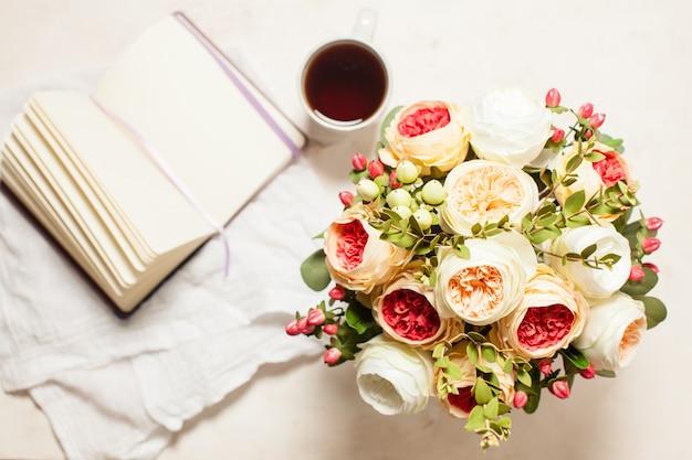 Una tazza di tè nero, taccuino e bellissimi fiori sul tavolo, vista dall'alto. il concetto di ispirazione alla creatività