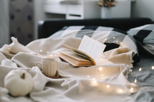 Una tazza e un libro colazione a letto con lenzuola e cuscini grigi weekend pigro dolce casa