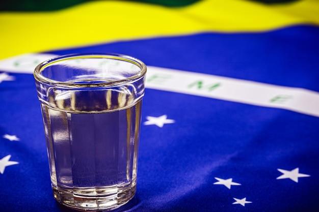 Tazza di cachaã§a o pinga brasiliano, con la bandiera brasiliana in background in occasione della giornata nazionale di cachaã§a