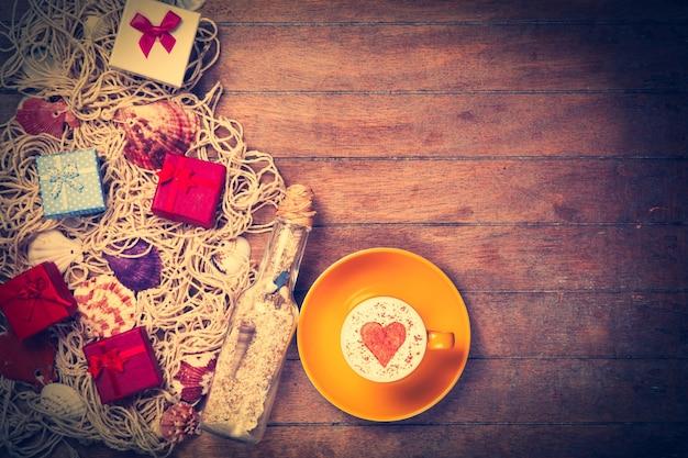 Tazza di cappuccino con simbolo a forma di cuore, regalo e rete con conchiglie e bottiglia su legno