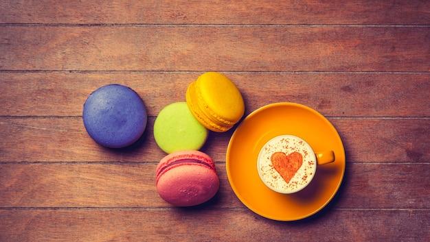Tazza di cappuccino con simbolo a forma di cuore e macarons su legno
