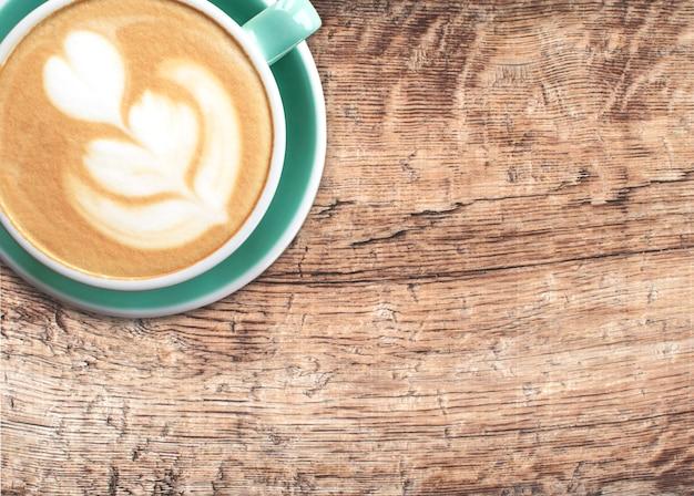 Una tazza di cappuccino con latte art su uno sfondo di legno. bella schiuma, tazza di ceramica verde. disposizione piatta.