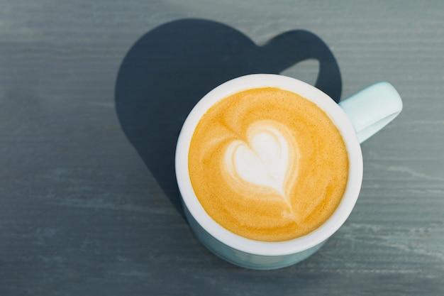 Tazza di cappuccino con latte art su fondo in legno. bella schiuma, tazza in ceramica azzurra. vista dall'alto, copia spazio per il testo.