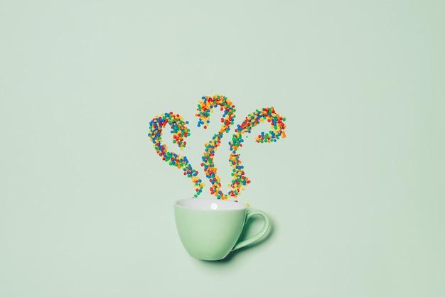 Tazza di cappuccino con il simbolo del fumo e caramelle su sfondo verde pastello