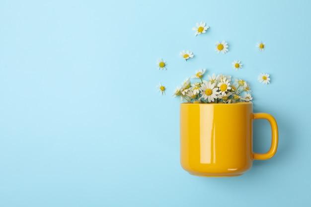 Tazza e camomilla su sfondo blu. tè alla camomilla