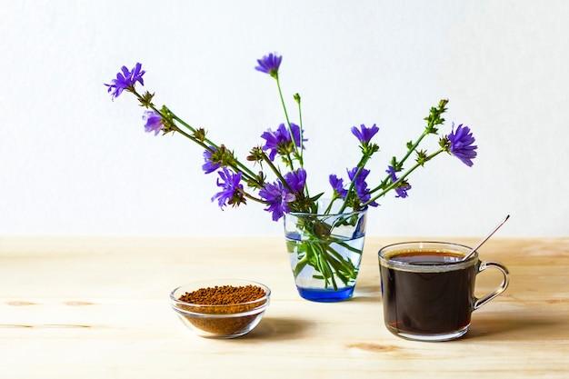 Una tazza di cicoria, granuli di cicoria istantanea liofilizzata e fiori blu