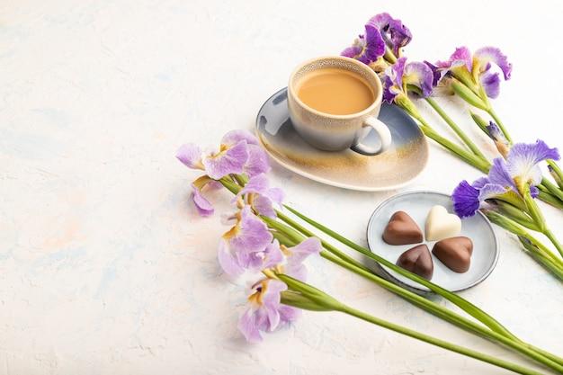 Tazza di cioffee con cioccolatini e fiori di iris lilla su fondo di cemento bianco.
