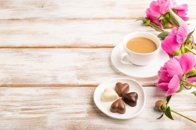 Tazza di cioffee con cioccolatini, fiori di peonia rosa su fondo di legno bianco.
