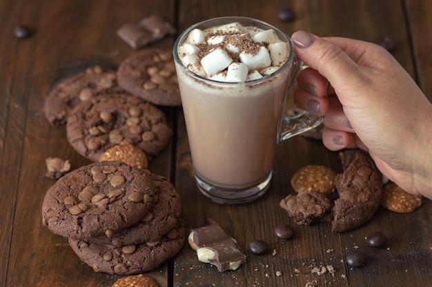 Tazza di cacao con caramelle gommosa e molle e biscotti al cioccolato su legno scuro