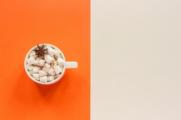 Tazza di cacao con caramelle gommosa e molle su beige arancio.