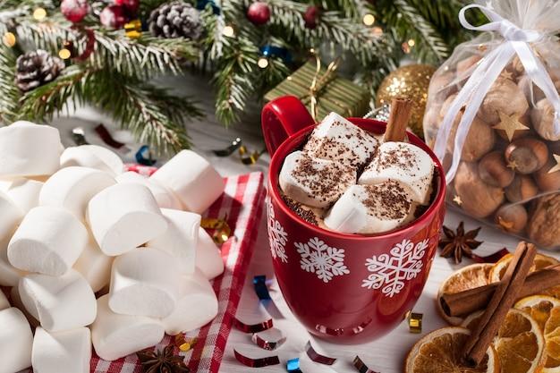 Tazza di cacao con marshmallow bianco e spuntini natalizi sulla tavola di natale