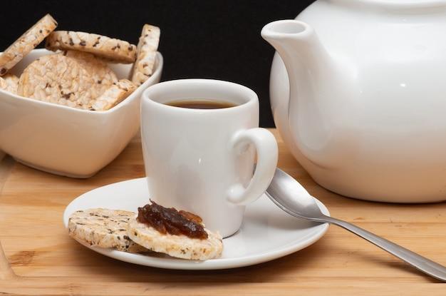 Tazza di caffè accanto a biscotti vegani di riso una ciotola piena di biscotti e una caffettiera sotto il tavolo di legno