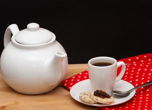 Tazza di caffè accanto a biscotti vegani di riso e una caffettiera sotto il tavolo di legno