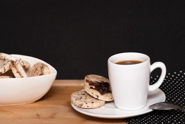 Una tazza di caffè accanto a biscotti vegani di riso con gelatina sulla parte superiore e una ciotola piena di biscotti di riso